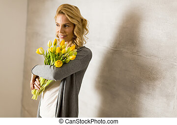 Young woman with a bouquet of yellow tulips