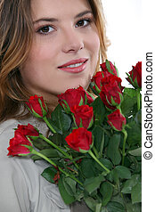 Young woman with a bunch of red roses