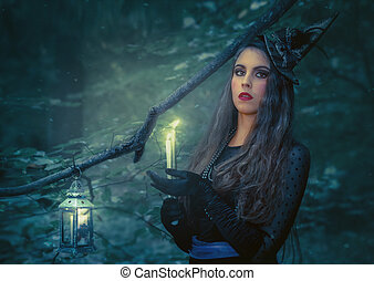 Young woman with a burning book in the forest. Halloween background.