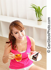 Young woman with a cake and tea