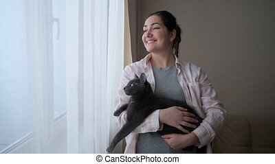 Young woman with a cat looking out the window