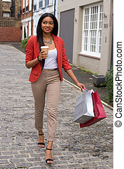 young woman with a coffee and shopping bags