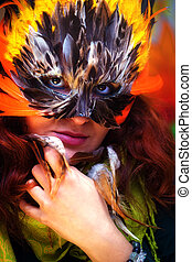 Young woman with a colorful feather carnival face mask eye