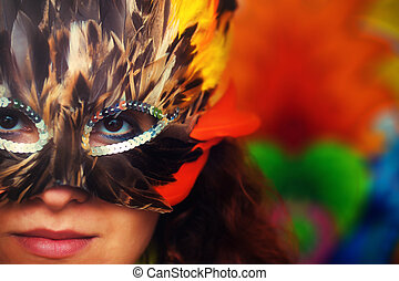 Young woman with a colorful feather carnival face mask on bright