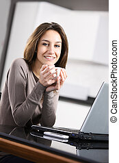 young woman with a cup of coffee and laptop