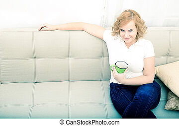 Young woman with a cup of coffee on the sofa