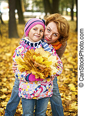 young woman with a daughter in autumn park