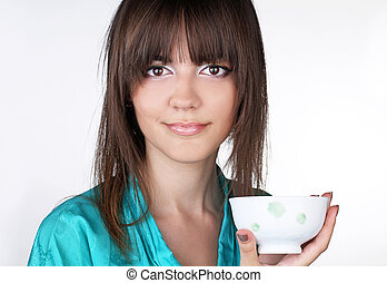 Young woman with a drinking bowl on white background