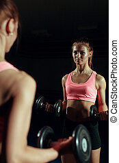 Young woman with a dumbbell in the gym.