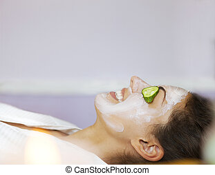 Young woman with a facial mask and cucumber on her face