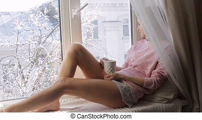 Young woman with a hot cup ot tea sitting on window sill. Winter