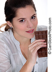 Young woman with a huge bar of chocolate
