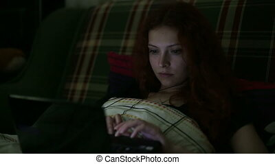 Young woman with a laptop answers the phone lying on the bed at home in the night