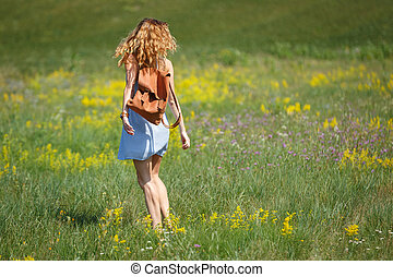 Young woman with a leather backpack in a summer field
