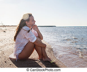 Young woman with a pensive look sits on the seashore. The concept of meditation, meditation, expectation, loneliness