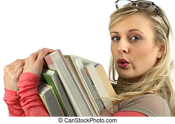 Young woman with a pile of books in her arms