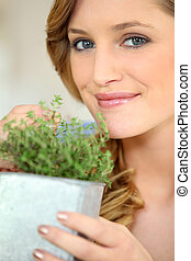 Young woman with a pot of thyme