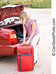 young woman with a red suitcase in the car