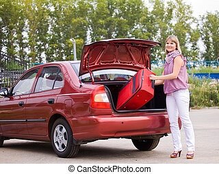 young woman with a red suitcase in the car - young woman ...