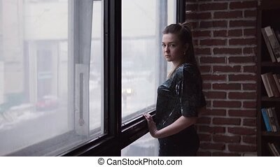 Young woman with a sad look is standing by the window