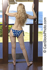 young woman with a slender waist and wide hips in a swimsuit  stand on a terrace and looks at the sea