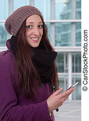 Young woman with a smart phone in town