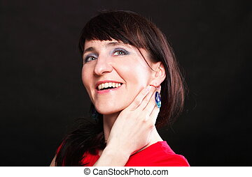 Young woman with a smile shows the earrings