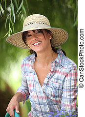 young woman with a straw hat is watering in her kitchen garden