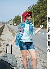 Young woman with a suitcase is hitchhiking on road near the sea