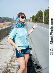 Young woman with a suitcase is hitchhiking on the road