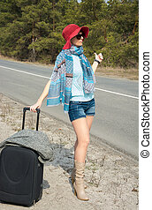 Young woman with a suitcase is hitchhiking on the road pointing
