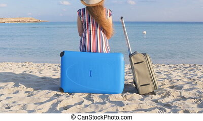 Young woman with a suitcase sitting on the beach