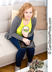 Young woman with a Tablet PC on the Sofa