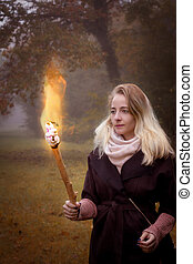 Young woman with a torch in hands.