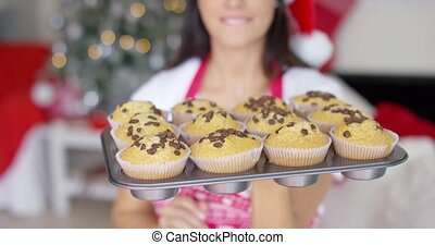Young woman with a tray of Christmas cupcakes