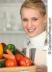 Young woman with a tray of fresh vegetables