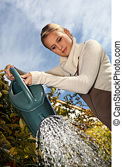 Young woman with a watering can