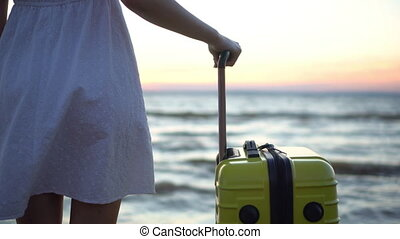 Young woman with a yellow suitcase on the beach by the sea. A girl in a white dress looks at the sunset close-up.