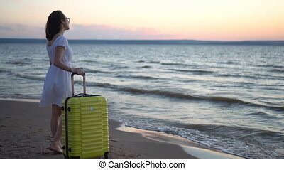 Young woman with a yellow suitcase on the beach by the sea. A girl in a white dress looks at the sunset.