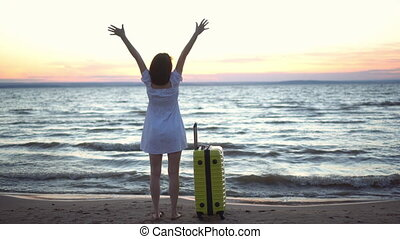 Young woman with a yellow suitcase on the beach by the sea. A girl in a white dress looks at the sunset and raises her hands with joy.