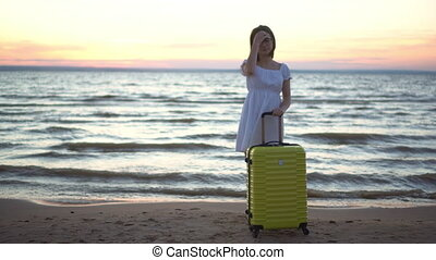 Young woman with a yellow suitcase on the beach by the sea. Girl in a white dress by the sea at sunset.