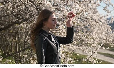Young woman with allergy symptoms, sneezing, blowing her nose, springtime slow motion