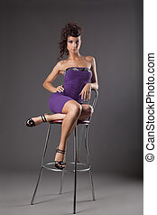young woman with amazing figure sit on chair
