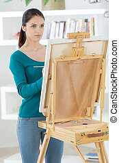 young woman with an easel paints a picture