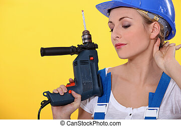 Young woman with an electric drill