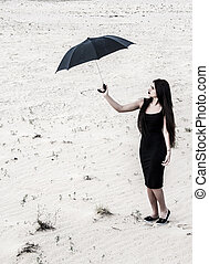 Young woman with an umbrella in a desert