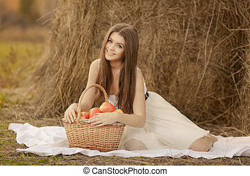 young woman with aplle basket outdoor