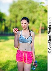Young woman with apple after running outside. Female fitness model training outside in the park. Healthy wellness fitness lifestyle.
