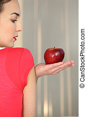 Young woman with apple in hand