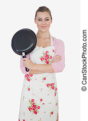 Young woman with arms crossed holding frying pan